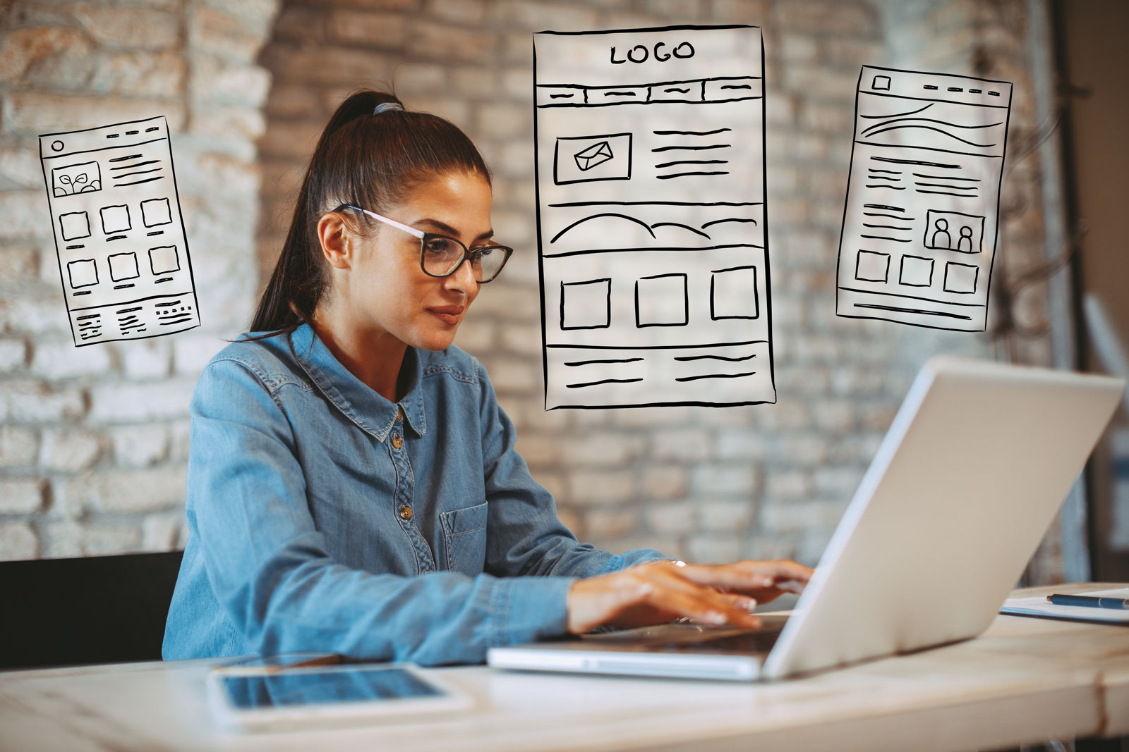 woman with glasses working on computer surrounded by wireframe drawings of websites